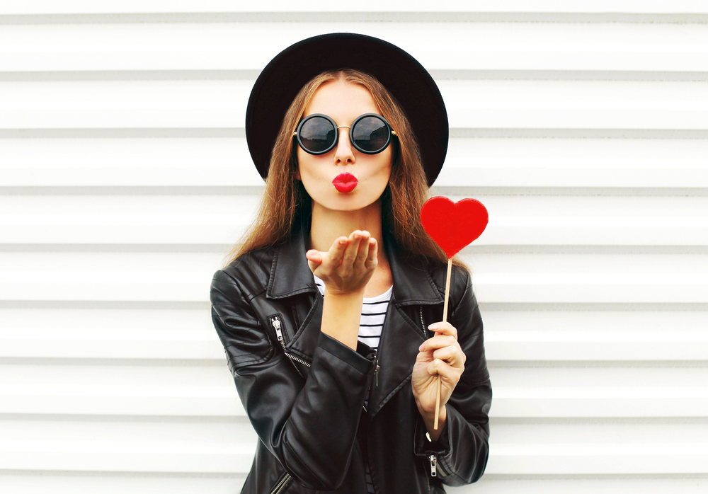 Girl in sunglasses blowing a kiss