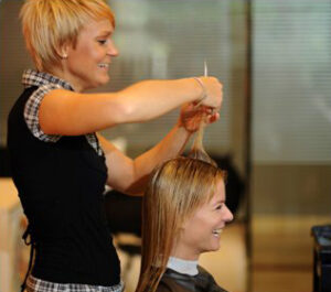 Woman cutting hair at Bellus Academy
