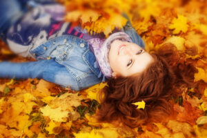 Girl rolling in a pile of leaves in the fall