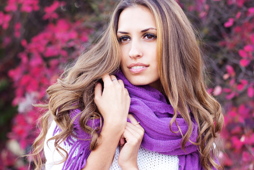 Woman in a scarf in front of purple flowers