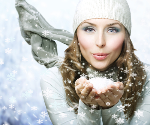 A wintery women with chilling makeup blows a mist of magically identical snowflakes