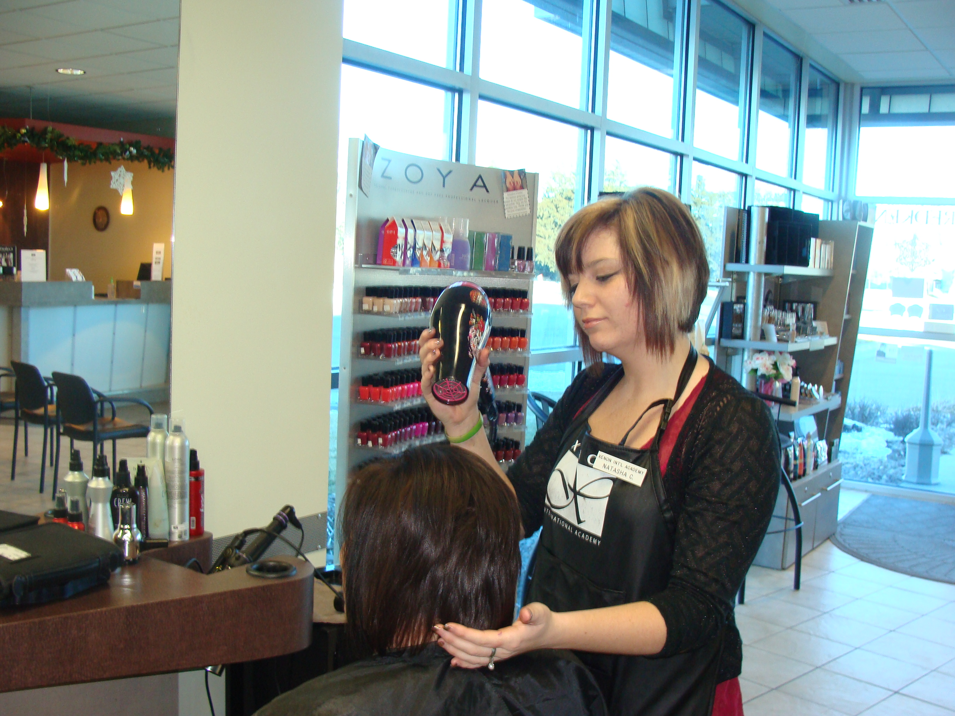A woman blowdries hair at Xenon Academy