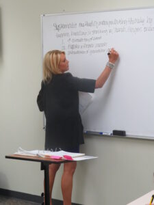 Instructor writing on the whiteboard at Xenon Academy