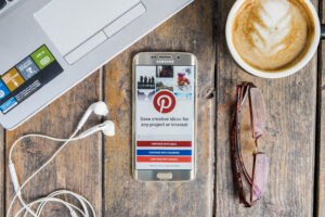 Pinterest application open on samsung phone with other desk supplies