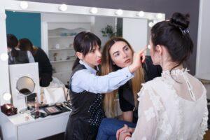 teacher teaching makeup to a student in beauty school