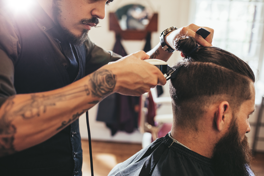 barber trims the back of his client's hair with clippers