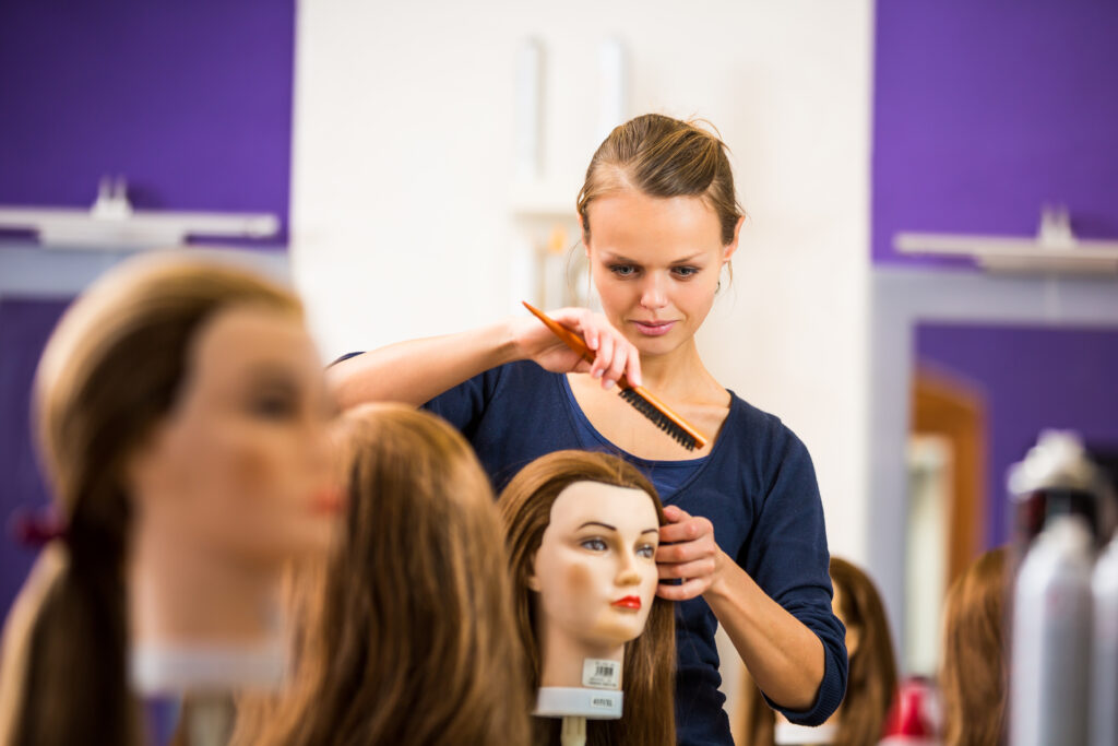 A woman working on a false head in a student salon