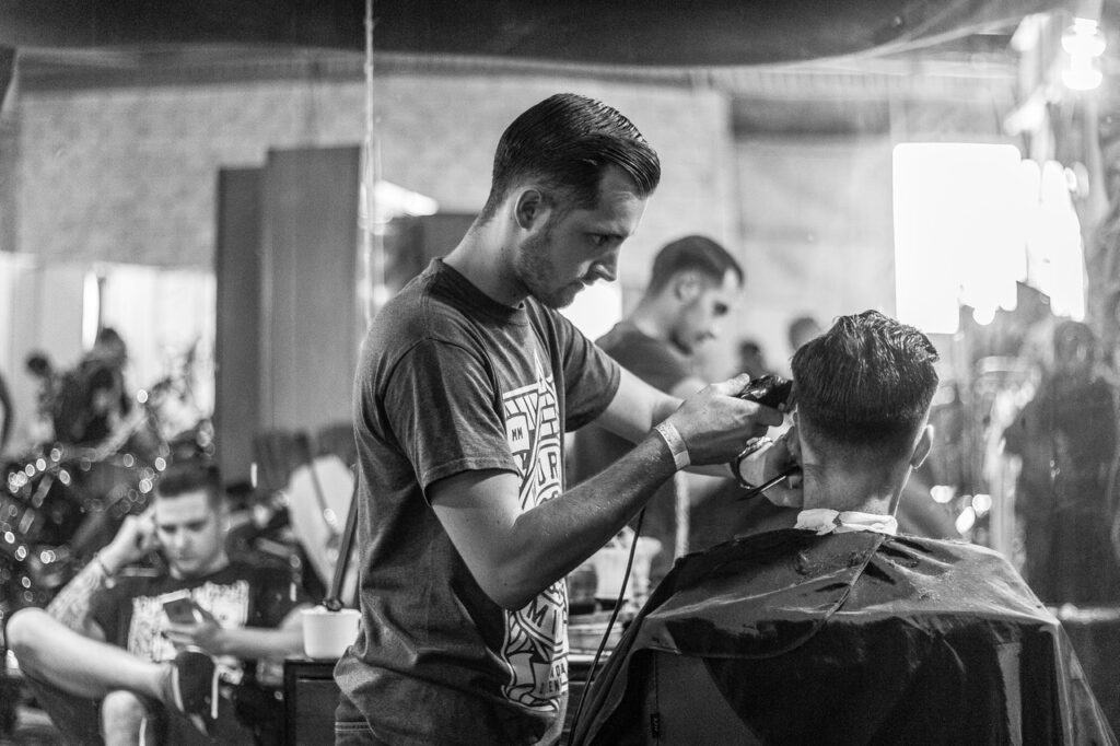 barber giving a client a haircut using clippers in a barbershop in black and white