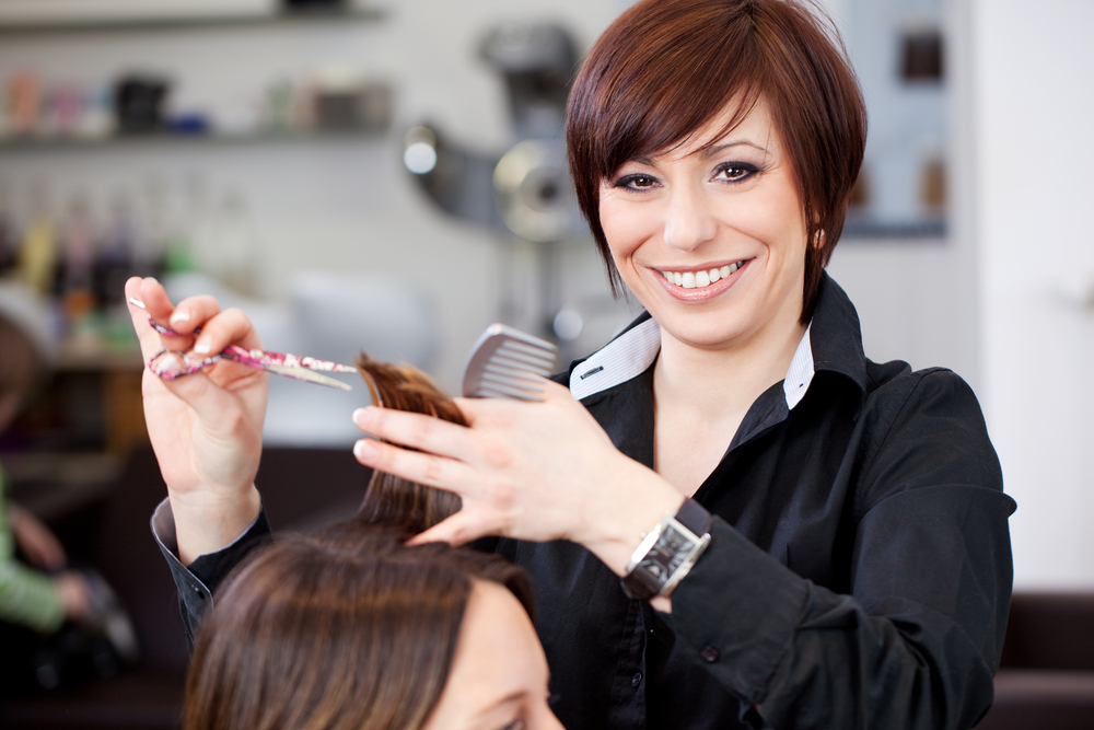red haired cosmetologist cutting hair