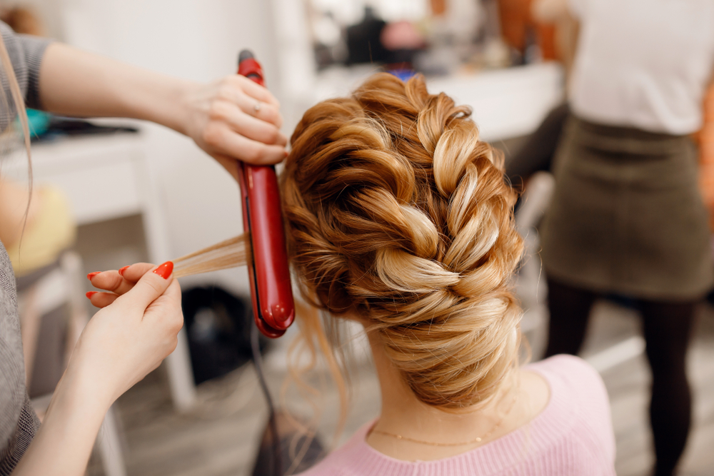 a cosmetology student does the hair of a woman for an event