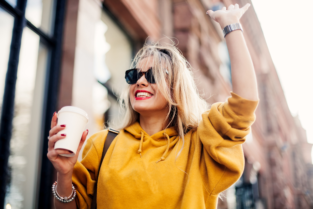 Excited blonde woman holding coffee while walking and raising hand