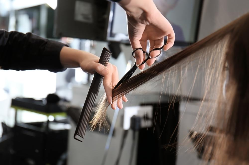 woman trimming another woman's hair in a salon