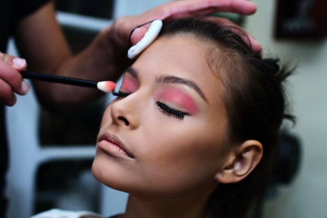 stylist applies pink eyeshadow on client