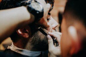 Barber shaving clients beard